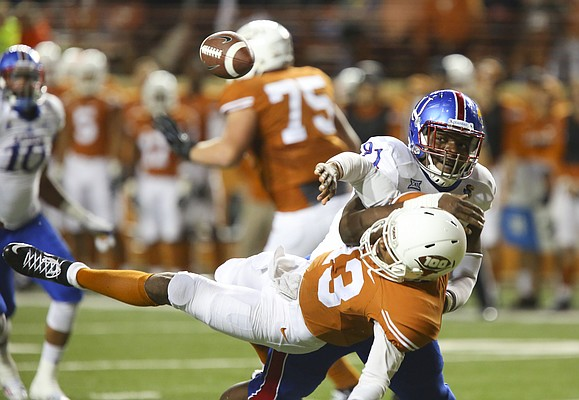 Kansas defensive tackle D.J. Williams (91) lays out Texas quarterback Jerrod Heard (13) and forces a fumble during the second quarter on Saturday, Nov. 7, 2015 at Darrell K. Royal Stadium in Austin, Texas.