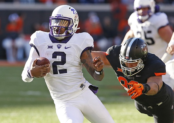 TCU quarterback Trevone Boykin (2) avoids a tackle by Oklahoma State's Trace Clark, right, during the Cowboys' 49-29 win Saturday in Stillwater, Oklahoma. The Horned Frogs host Kansas at 11 a.m. Saturday at Amon G. Carter Stadium in Fort Worth, Texas.