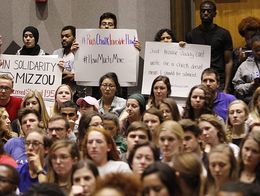 Students hold signs in the back of Woodruff Auditorium in the Kansas Union during a town hall forum on race. The group later took the stage and read a list of diversity and inclusion related demands for the KU campus. KU scheduled Wednesday afternoon's forum in the wake of problems at the University of Missouri, where the system president and chancellor resigned Monday under pressure from students who said the school failed to properly respond to racial problems there.