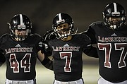 Lawrence High School senior quarterback Alan Clothier stands with his teammates during the alma matter following Lawrence's season-ending 42-17 loss to Blue Valley in Class 6A sectionals.