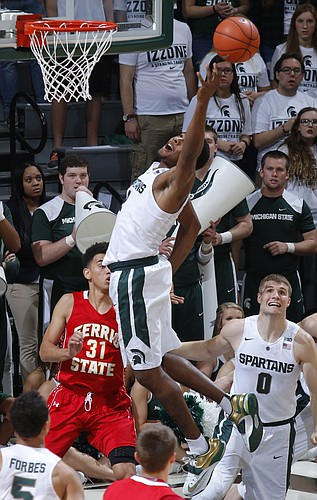 Michigan State's Javon Bess, center, reaches for a rebound over Ferris State's Peter Firlik (32) and Michigan State's Kyle Ahrens (0) during the first half of an NCAA college basketball exhibition game, Monday, Nov. 9, 2015, in East Lansing, Mich. (AP Photo/Al Goldis)