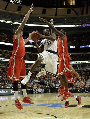 Michigan State's Lourawls Nairn Jr. (11) passes as he drives between Ohio State's Amir Williams, left, and Jae'Sean Tate, right, in the first half of an NCAA college basketball game in the quarterfinals of the Big Ten Conference tournament in Chicago, Friday, March 13, 2015. (AP Photo/Nam Y. Huh)