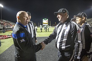 Kansas cornerbacks coach Kenny Perry shakes hands with officials at Southlake, Texas.
