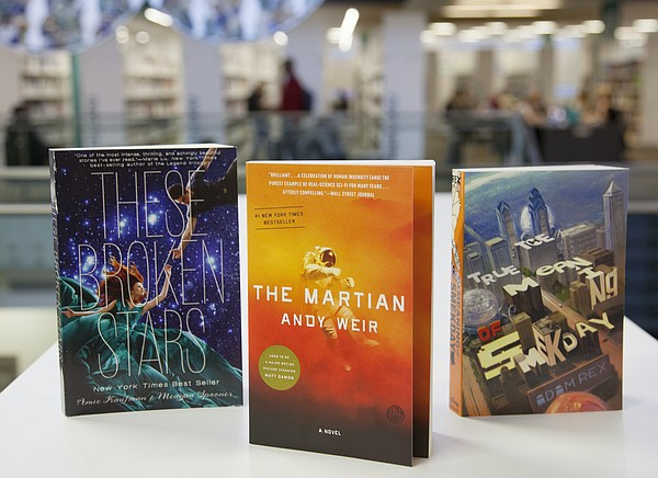 """The 2016 Read Across Lawrence event will feature, from left, """"These Broken Stars,"""" by Amie Kaufman (for teens), """"The Martian,""""by Andy Weir (for adults) and """"The True Meaning of Smekday,"""" by Adam Rex (for children)."""