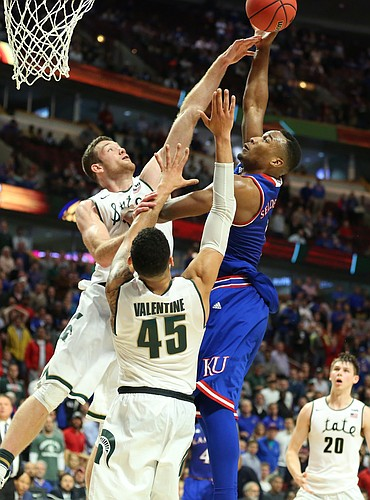 Kansas guard Wayne Selden Jr. (1) tries to put up a shot with seconds remaining over Michigan State forward Matt Costello  and guard Denzel Valentine (45) during the second half, Tuesday, Nov. 17, 2015 at United Center in Chicago.