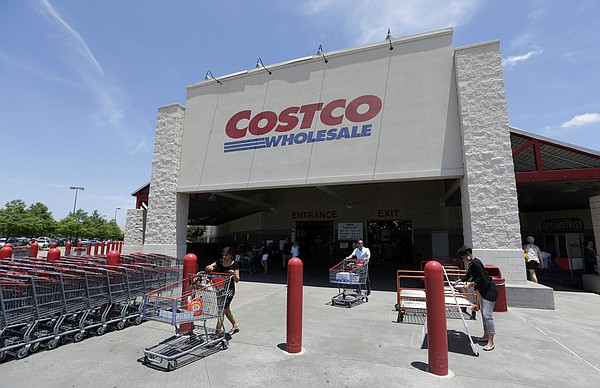In this June 4, 2014 photo, shoppers push carts out of a Costco in Plano, Texas.
