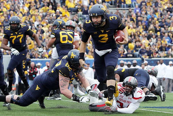 West Virginia quarterback Skyler Howard (3) avoids Texas Tech linebacker D'Vonta Hinton (34) during the first half of an NCAA college football game, Saturday, Nov. 7, 2015, in Morgantown, W.Va. (AP Photo/Raymond Thompson)
