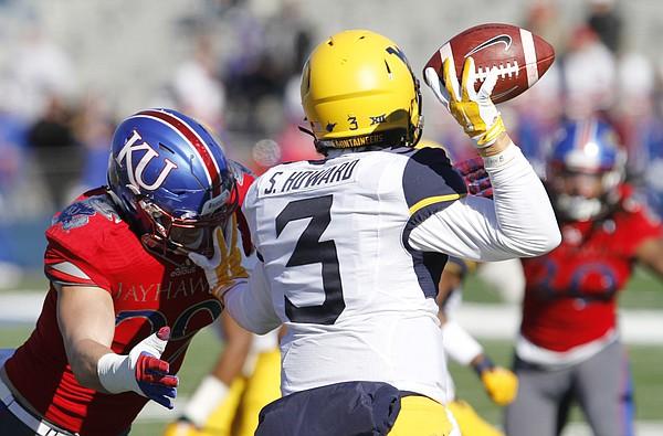 Kansas linebacker Joe Dineen, Jr., left, pursues West Virginia quarterback Skyler Howard (3) in the first-half against the Mountaineers Saturday, Nov. 21, 2015, at Memorial Stadium.