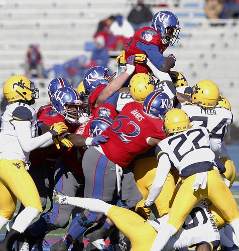 Kansas running back Ke'aun Kinner rides atop his teammates and West Virginia defenders as the Jayhawks push for yards in a 49-0 loss to the Mountaineers Saturday, Nov. 21, 2015, at Memorial Stadium.