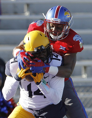 Kansas freshman wide receiver Jeremiah Booker, top, tries to wrestle away an interception by West Virginia cornerback Nan Kyeremeh, (14) during the Jayhawks 49-0 loss to the West Virginia Mountaineers Saturday, Nov. 21, 2015, at Memorial Stadium.