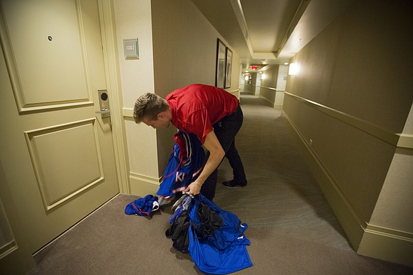 Manager Chip Kueffer retrieves a pile of uniforms left outside a player's room for pickup following the Jayhawks' 123-72 win, Monday, Nov. 23, 2015 at the Westin Maui in Lahaina, Hawaii.