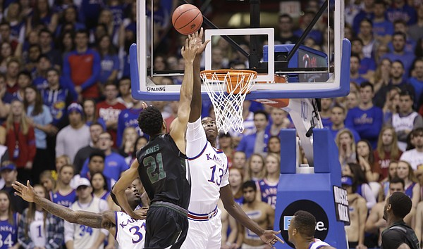 Kansas forward Cheick Diallo (13) gets a hand up in front of a shot by Loyola forward Jarred Jones (21) during the first half, Tuesday, Dec. 1, 2015 at Allen Fieldhouse.