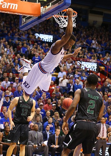 Kansas guard Wayne Selden Jr. (1) hangs on the rim after delivering a dunk against Loyola during the first half, Tuesday, Dec. 1, 2015 at Allen Fieldhouse.