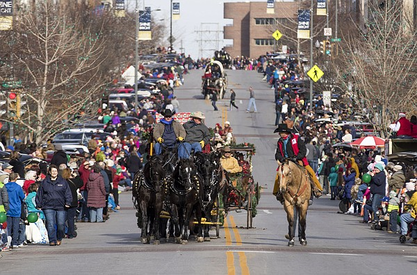 Thousands of spectators line both sides of Massachusetts Street as horse drawn carriages go past during the 23rd annual Lawrence Old-Fashioned Christmas Parade on Saturday.