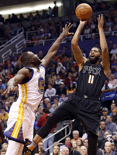Phoenix Suns forward Markieff Morris (11) shoots over Golden State Warriors forward Draymond Green during the third quarter of an NBA basketball game, Friday, Nov. 27, 2015, in Phoenix. The Warriors won 135-116. (AP Photo/Rick Scuteri)