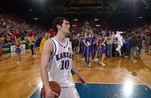 This file photo shows a handful of KU fans celebrating on the court behind former Jayhawk after KU's thrilling victory over No. 3 Texas in January 2003.