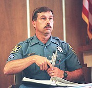 In this file photo from 2000, Jefferson County Sheriff's Office Sgt. Robert Poppa holds a 9mm gun that KBI officials identified as the gun that killed Camille Arfmann.