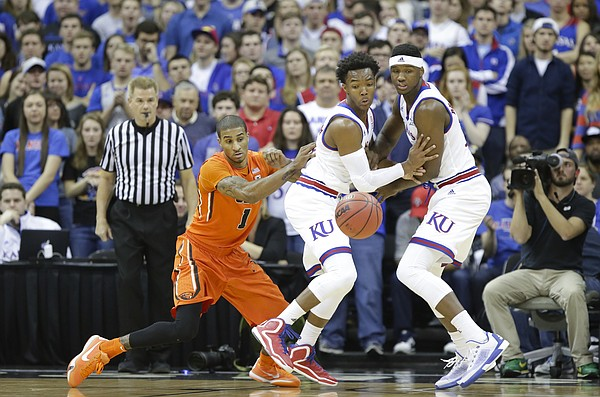 Kansas guard Devonte' Graham, forward Carlton Bragg Jr., and Oregon State guard Gary Payton II (1) vie for a loose ball during the first half, Saturday, Dec. 12, 2015 at Sprint Center.