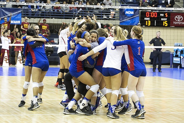 Kansas University volleyball players rush the court after their Elite Eight victory over USC.