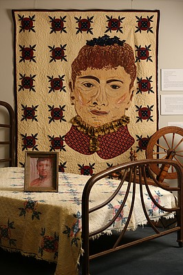 "A portrait of a slave Maria Rodgers Martin, born in 1831, sits on a bed that is made with one of her quilts, Dec. 15, 2015, at the African American Quilt Museum and Textile Academy, 2001 Haskell Ave. Behind the bed on the wall hangs a quilt, ""A Tribute to Maria Rodgers Martin"" made as a collaborative effort by artists Marla Jackson, Tonia Johnson and several students."