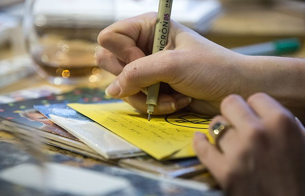 A letter is written during a Wonder Fair Letter Writing Club at Decade coffee shop, 920 Delaware Street on Sunday, Dec. 13, 2015.