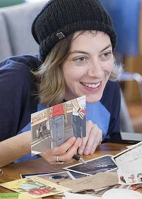 Carly Efros, of Lawrence, holds up a postcard as she looks through stationery and chats with other club members during a Wonder Fair Letter Writing Club meeting at Decade coffee shop, 920 Delaware Street on Sunday, Dec. 13, 2015.