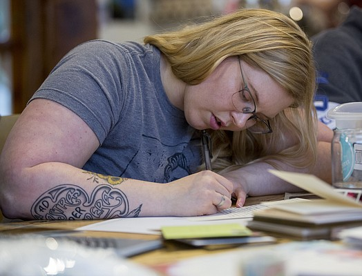 Renee Whaley, of Lawrence, thoughtfully chooses her words as she pens a letter during a Wonder Fair Letter Writing Club meeting at Decade coffee shop, 920 Delaware Street on Sunday, Dec. 13, 2015.