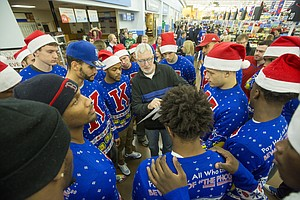 Kansas basketball players huddle around Roger Morningstar as he gives out the Christmas lists of local families in need so the players can shop for the families at Wal-Mart, 3300 Iowa Street, on Wednesday evening.