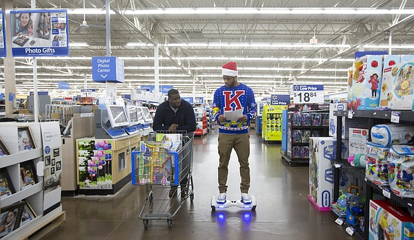 Kansas assistant coach Jerrance Howard walks beside hoverboard-bound junior Frank Mason III as they shop for a local family at Wal-Mart, 3300 Iowa Street, on Wednesday evening, Dec. 16, 2015.