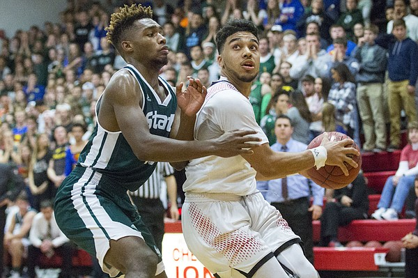 Free State senior Chrision Wilburn, left, defends Lawrence High senior Justin Roberts, right, while Roberts eyes the basket during their game Friday evening at LHS.