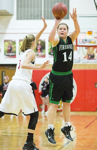 Free State junior Madison Piper (14 ) lines up a three point shot over Lawrence High junior Skylar Drum (3) during their game Friday evening at LHS.