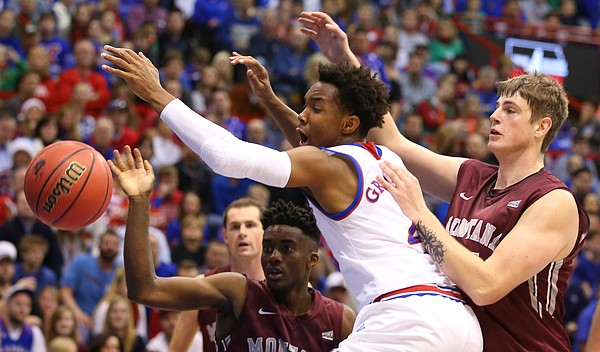 Kansas guard Devonte' Graham (4) fights for a loose ball with Montana guard Michael Oguine, left, and center Bryden Boehning (35) during the first half, Saturday, Dec. 19, 2015 at Allen Fieldhouse.