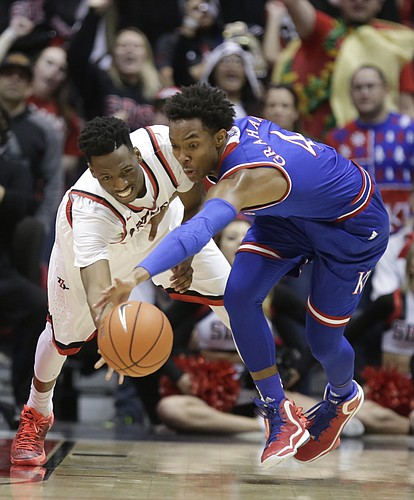Kansas guard Devonte' Graham (4) and San Diego State guard Dakarai Allen (4) battle for a loose ball during the first half, Tuesday, Dec. 22, 2015 at Viejas Arena in San Diego.