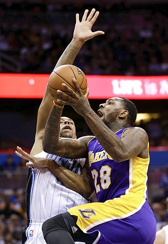 Los Angeles Lakers center Tarik Black (28) goes to the basket past Orlando Magic forward Channing Frye during the first half of an NBA basketball game, Wednesday, Nov. 11, 2015, in Orlando, Fla. (AP Photo/John Raoux)