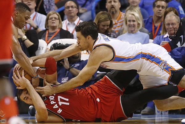 Oklahoma City Thunder guard Russell Westbrook, left, and forward Nick Collison, right, try to take the ball away from Toronto Raptors center Jonas Valanciunas (17) in the third quarter of an NBA basketball game in Oklahoma City, Wednesday, Nov. 4, 2015. Toronto won 103-98. (AP Photo/Sue Ogrocki)