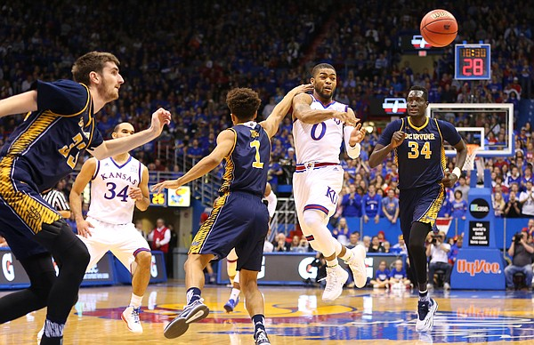 Kansas guard Frank Mason III (0) throws a pass to the wing around UC Irvine guard Alex Young (1) during the second half, Tuesday, Dec. 29, 2015 at Allen Fieldhouse.