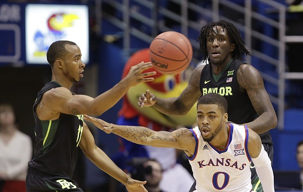 Kansas guard Frank Mason III (0) defends against a pass from Baylor guard Lester Medford (11) during the second half, Saturday, Jan. 2, 2016 at Allen Fieldhouse. In back is Baylor forward Taurean Prince (21).