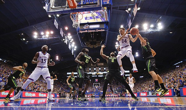 Kansas guard Brannen Greene (14) hangs to dish off a pass to orward Carlton Bragg Jr. (15) during the second half, Saturday, Jan. 2, 2016 at Allen Fieldhouse.
