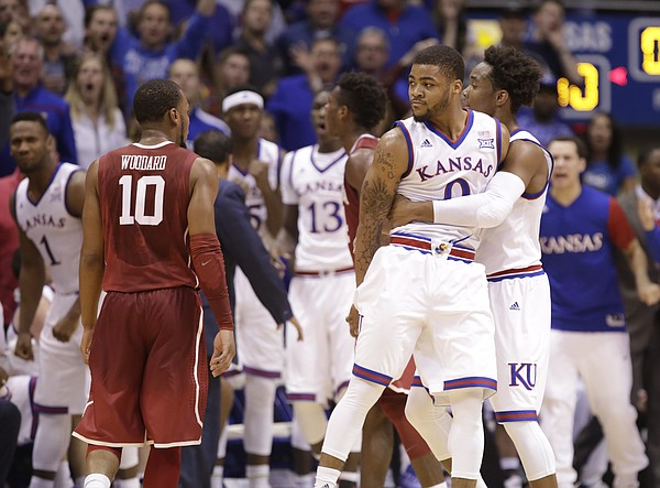 Kansas guard Frank Mason III (0) is held back by Kansas guard Devonte' Graham (4) after he was whistled for a foul on Oklahoma guard Buddy Hield (24) with seconds remain during the first half, Monday, Jan. 4, 2016 at Allen Fieldhouse.
