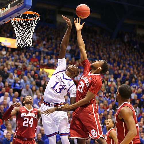 Kansas forward Cheick Diallo (13) tips a rebound out over Oklahoma forward Dante Buford (21) during the first half, Monday, Jan. 4, 2016 at Allen Fieldhouse. Also pictured are Oklahoma guard Buddy Hield (24) and guard Jordan Woodard, right.