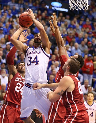 Kansas forward Perry Ellis (34) goes up for a bucket against Oklahoma guard Buddy Hield (24), forward Dante Buford (21) and forward Ryan Spangler (00) during the first half, Monday, Jan. 4, 2016 at Allen Fieldhouse.