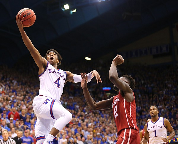 Kansas guard Devonte' Graham (4) gets a foul from Oklahoma guard Dinjiyl Walker (2) during the second half, Monday, Jan. 4, 2016 at Allen Fieldhouse.