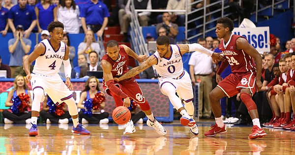 Kansas guard Frank Mason III (0) tries to steal the ball from Oklahoma guard Jordan Woodard (10) during the second half, Monday, Jan. 4, 2016 at Allen Fieldhouse. Also pictured are Kansas guard Devonte' Graham (4) and Oklahoma guard Buddy Hield (24).