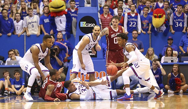 Kansas forward Landen Lucas (33) wrestles away a ball from Oklahoma guard Jordan Woodard (10) and tosses it to Kansas guard Devonte' Graham (4) late in the third overtime, Monday, Jan. 4, 2016 at Allen Fieldhouse.
