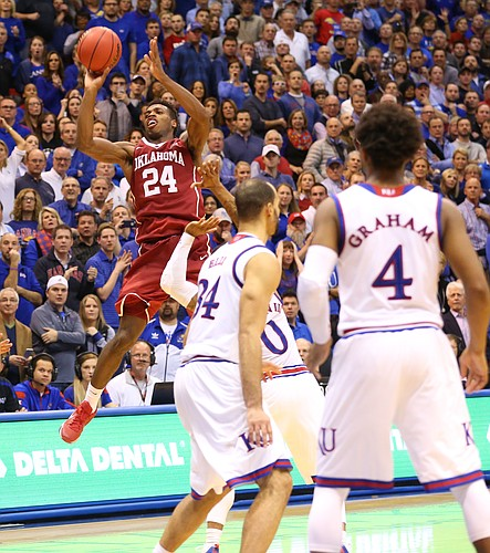 Oklahoma guard Buddy Hield (24) puts up a shot while guarded by Kansas guard Frank Mason III (0) with seconds remaining in the game during the second half, Monday, Jan. 4, 2016 at Allen Fieldhouse.