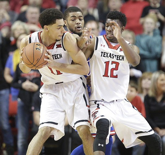Kansas guard Frank Mason III tries to cut between Texas Tech forward Zach Smith (11) and guard Keenan Evans (12) for an attempted steal during the second half, Saturday, Jan. 9, 2016 at United Spirit Arena in Lubbock, Texas.