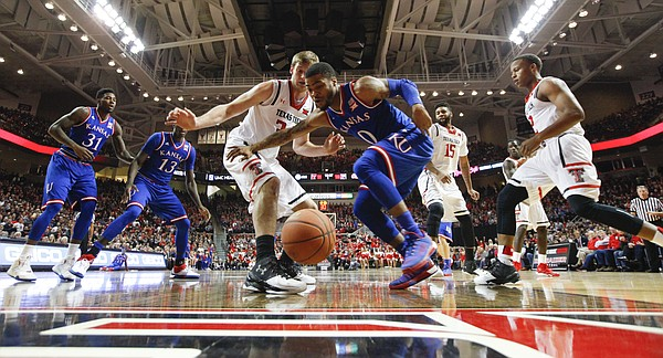 Kansas guard Frank Mason III (0) and Texas Tech forward Matthew Temple (34) hustle for a loose ball under the bucket during the first half, Saturday, Jan. 9, 2016 at United Spirit Arena in Lubbock, Texas.