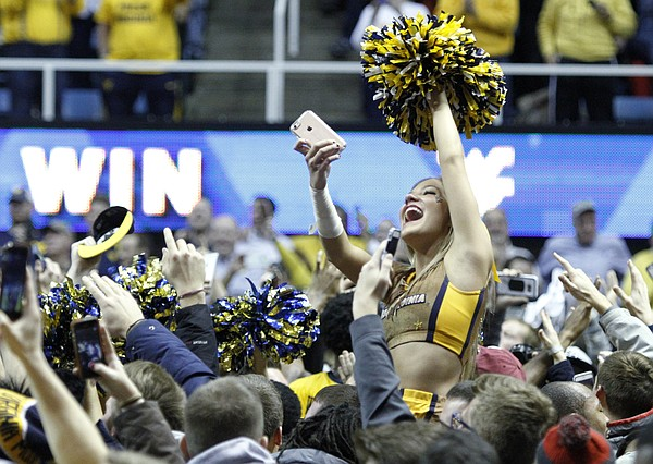 A West Virginia cheerleader rides on top of a crowd of fans as the rush the court after defeating the Jayhawks 74-63 at the WVU Colliseum in Morgantown, W.V. Tuesday.