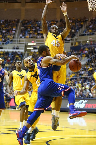 Kansas guard Frank Mason III, drives beneath West Virginia forward Elijah Macon (45) and is fouled by West Virginia guard Jaysean Paige (5), right, in the Jayhawks 74-63 loss to the Mountaineers at the WVU Colliseum in Morgantown, W.V. Tuesday.