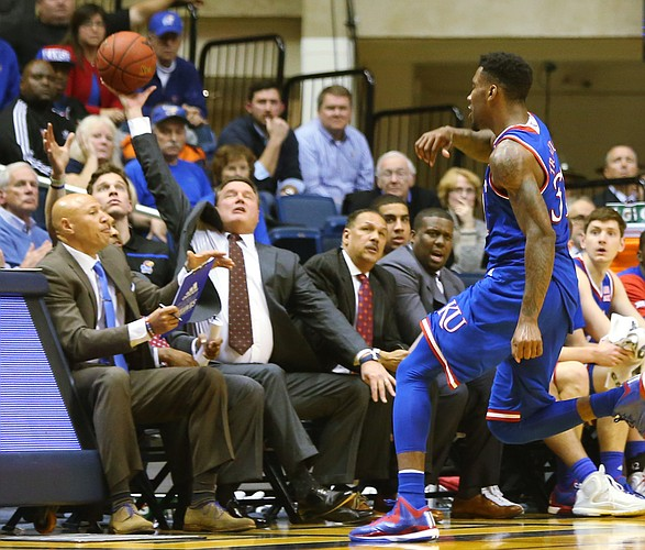 Kansas coach Bill Self tries to catch a loose ball as Kansas forward Jamari Traylor chased it out of bounds in a game between the Jayhawks and the Mountaineers in Morgantown, W.V. Tuesday.